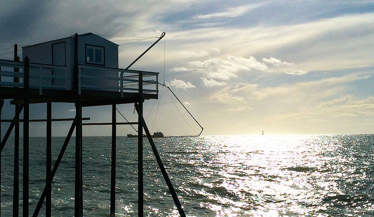 Photographie d'un bateau prisonnier du filet d'un carrelet à Saint Palais. Au loin le phare de Cordouan.